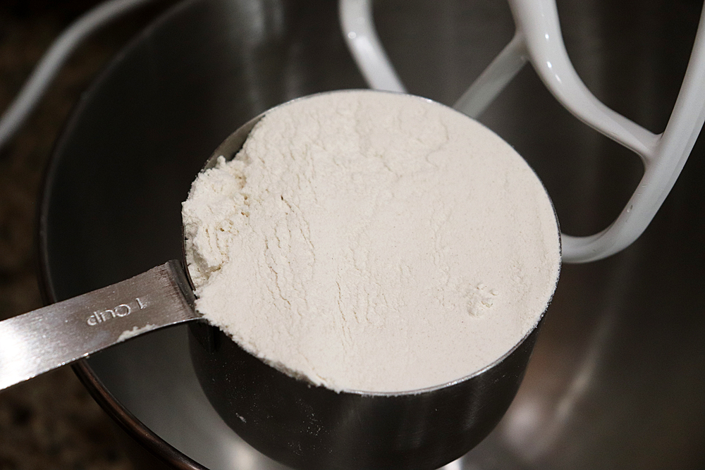 Adding flour to the bowl of an electric mixer