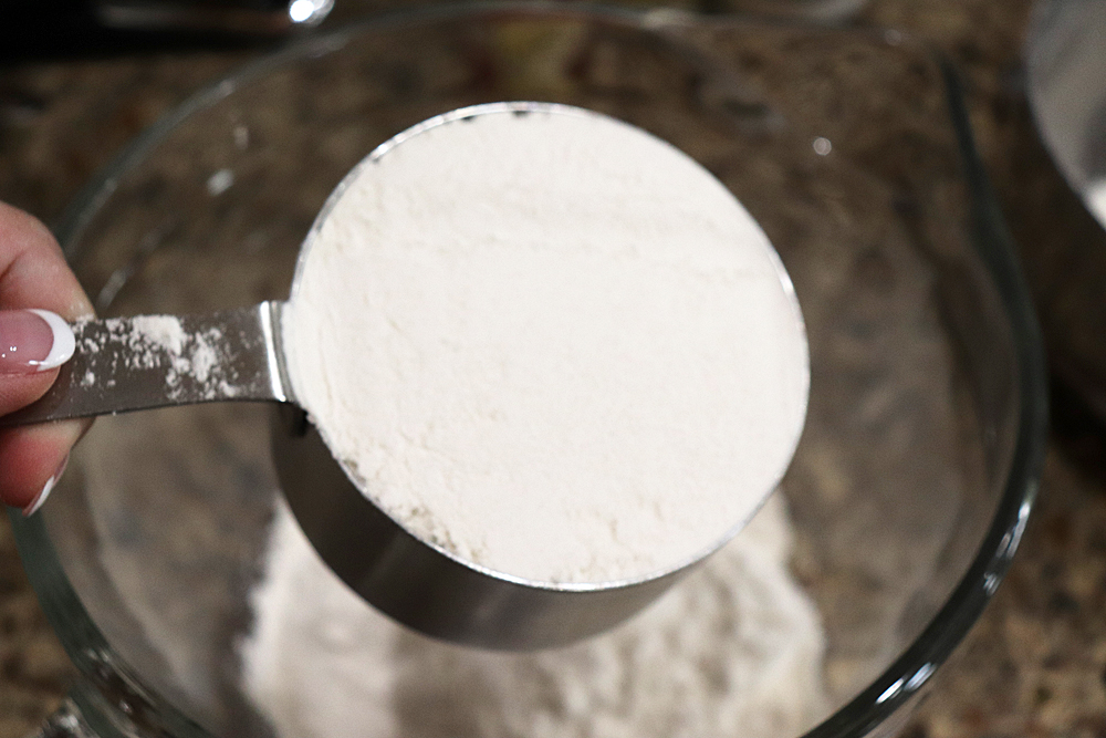 Adding flour to a mixing bowl