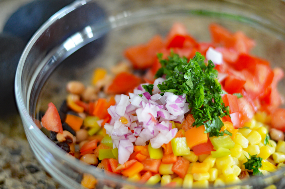 "Bowl of ingredients including red onion and parsley for Cowboy Caviar a/k/a ""Texas Caviar"""