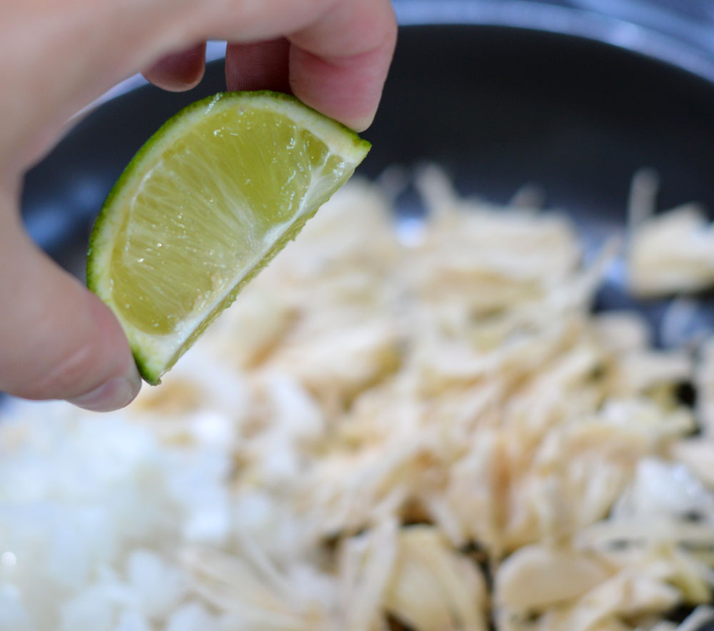 Adding a squeeze of lime to jackfruit garlic and onion
