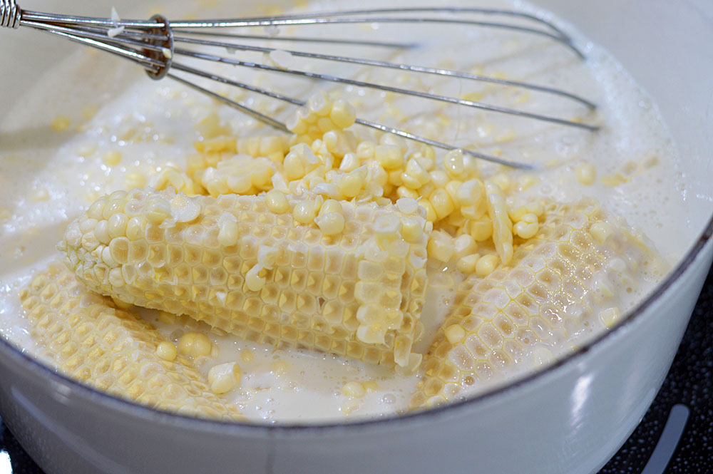 Boiling corn cobs in coconut milk