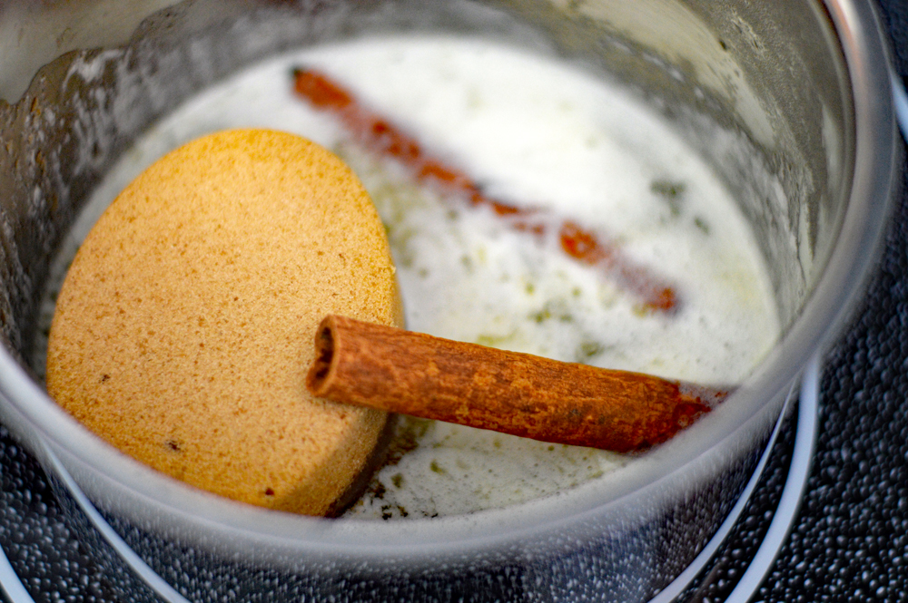 Pan with melted butter, sugar and cinnamon sticks for Classic Candied Sweet Potatoes Recipe