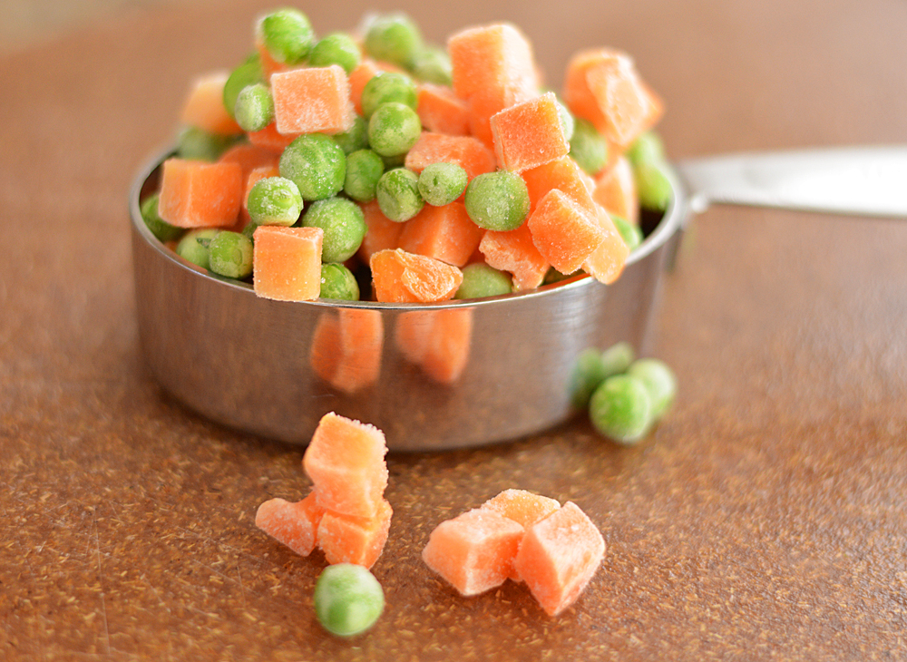 Peas and carrots in a measuring cup