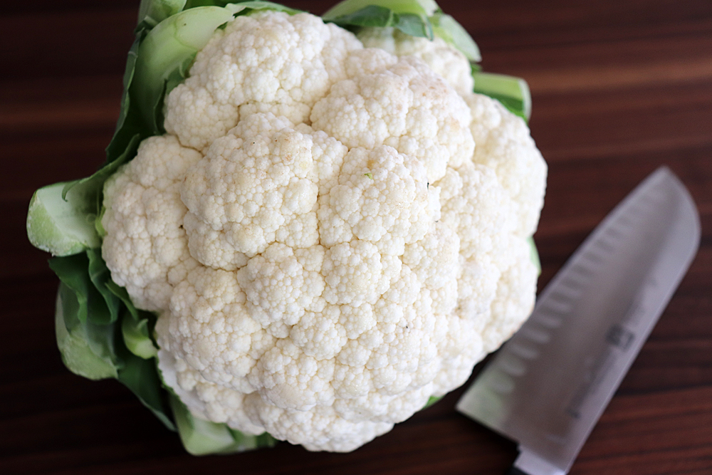 Head of cauliflower with knife on cutting board