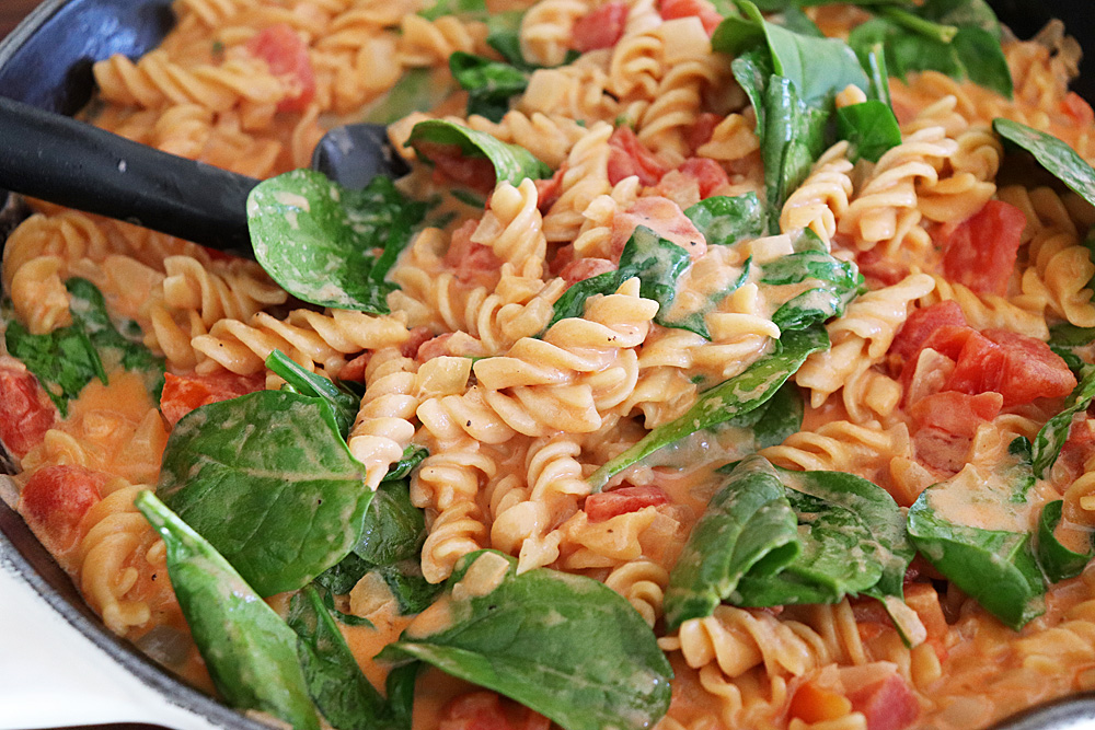 Wilted spinach in pasta with tomato cream sauce