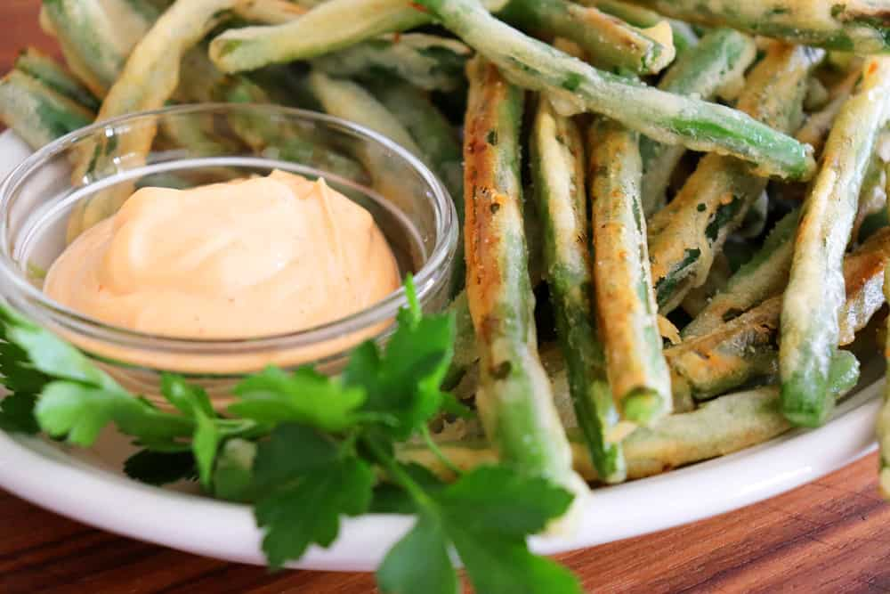 Close up of tempura green beans and dip with parsley