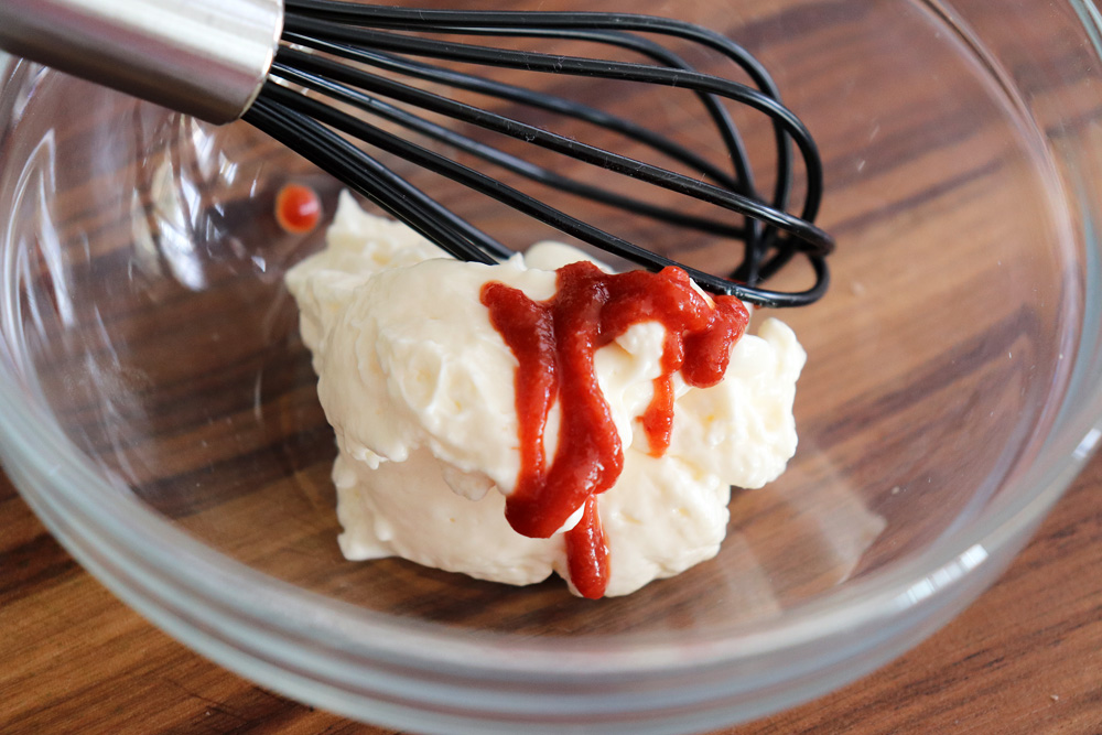 Combining mayonnaise and sriracha with a whisk