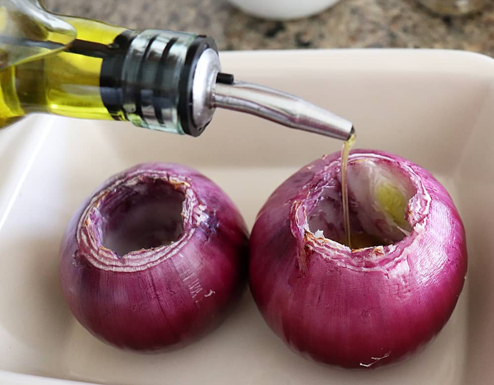 Drizzling olive oil on red onions for Emeril's Creamy Roasted Red Onions