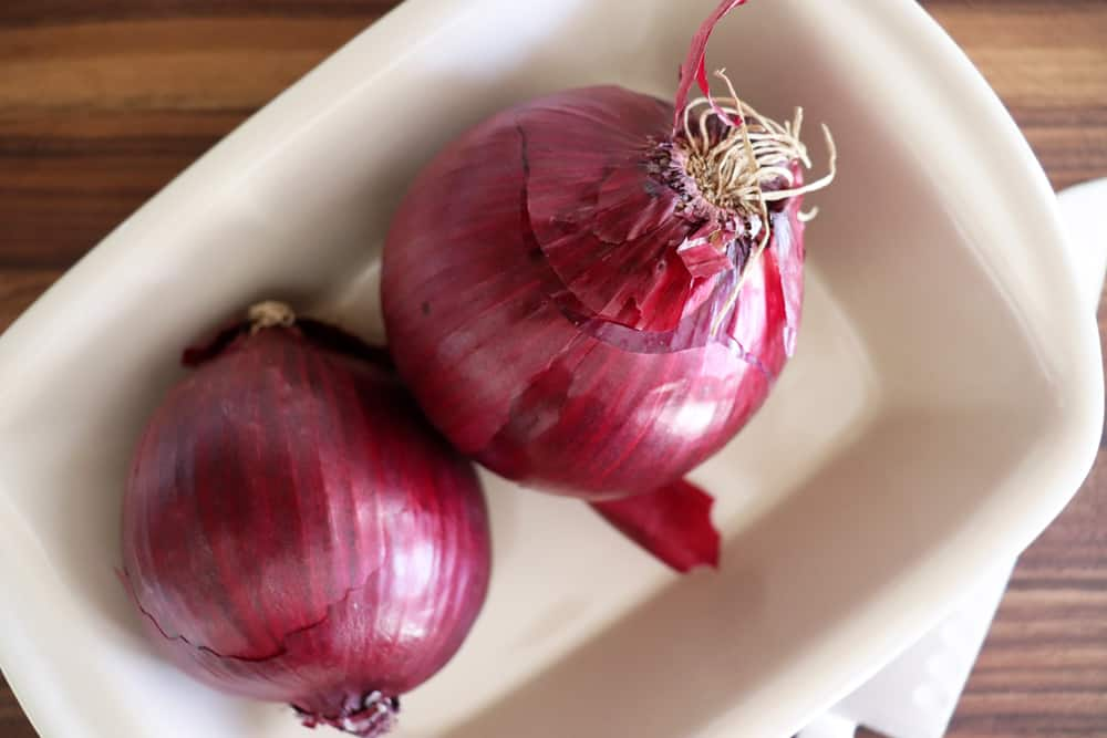 Red onions in a baking dish for Emeril's Creamy Roasted Red Onions
