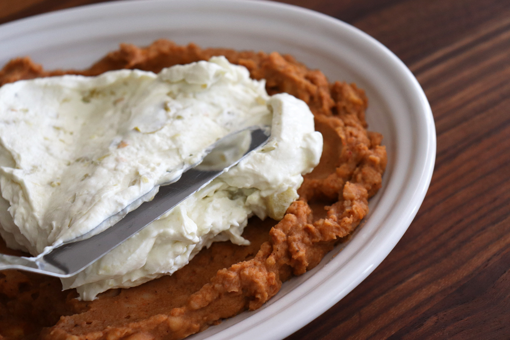 Spreading cream cheese layer onto refried beans