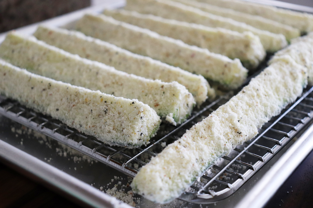 breaded zucchini strips on a rack