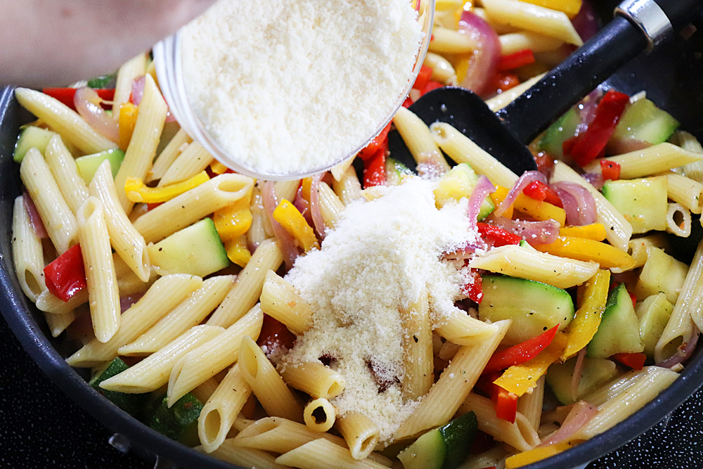 Adding parmesan to pasta and vegetables