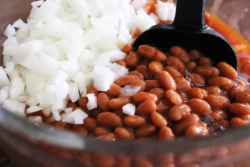 Vegetarian Baked Beans and white onion in a bowl