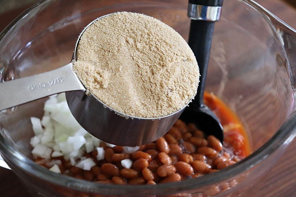 Adding brown sugar to the beans