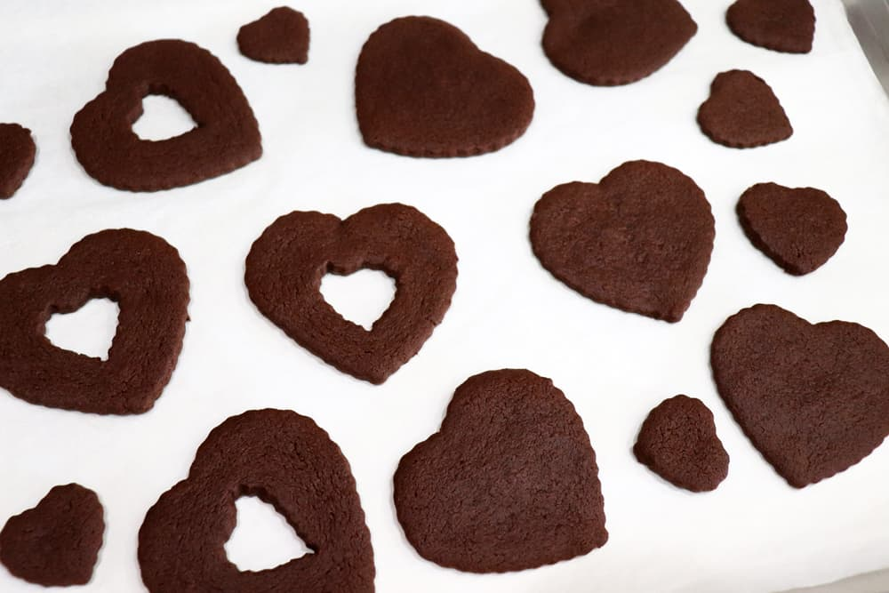 Vegan Chocolate Sugar Cookie dough cut into hearts on white parchment paper