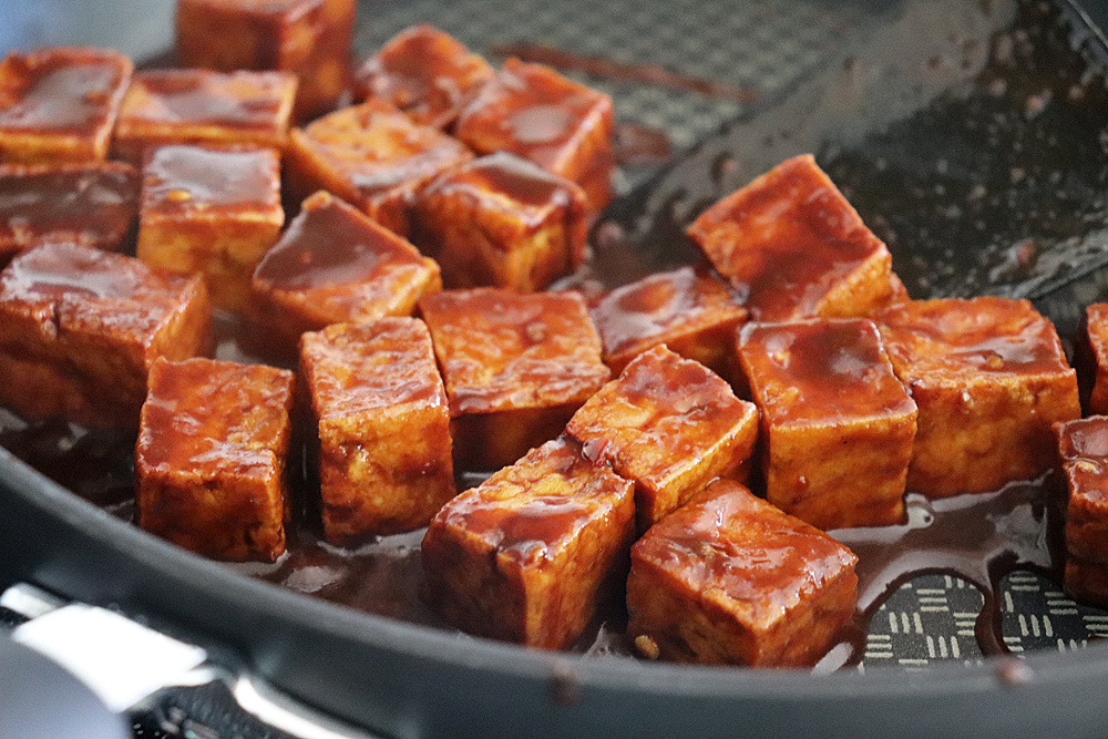 Tossing the tofu with the glaze until thickened