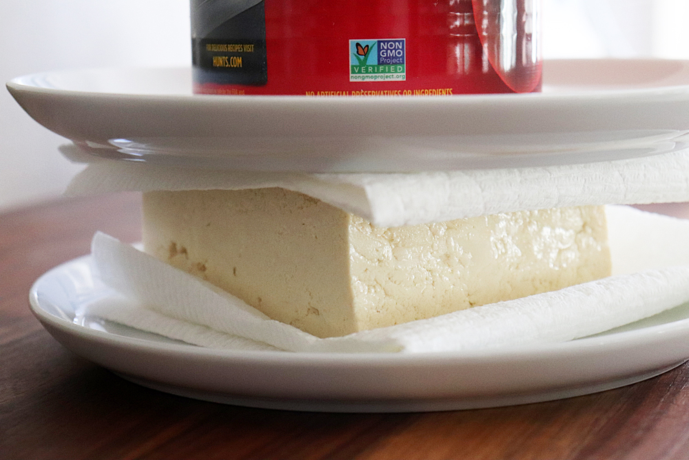 Pressing the tofu between two plates